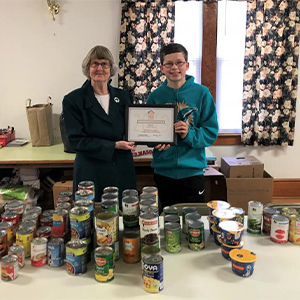Milton Community Food Pantry Board President presents certificate of thanks to Carter Barron.
