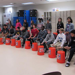 The Mariner bucket drummers practice with Ms. Keefer.