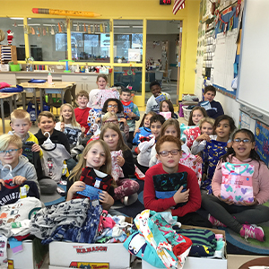 Mrs. Potter's class show off the 88 pairs of pajamas they collected.