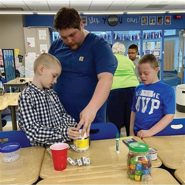 Paraprofessional Drew Colegrove helps students Styler Schwartz, left, and Luke Archer.
