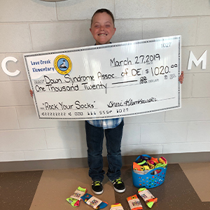 Love Creek Elementary student Luke Archer proudly displays the school's donation check