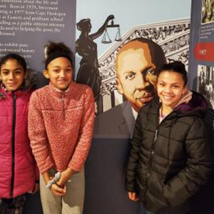 Ava Locust, Nariyah Perry, and Layeshca Arciliares pose by a rendering of Stevenson.