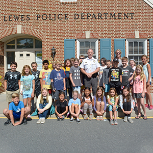 Chief of Lewes Police Department stands among the Shields CAP students.