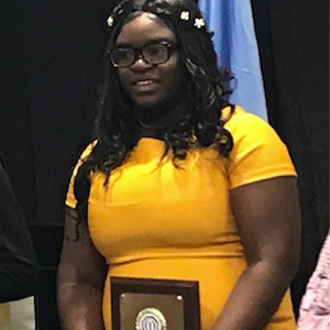 Sanchez Raymond holds her award for her oratorical skills.