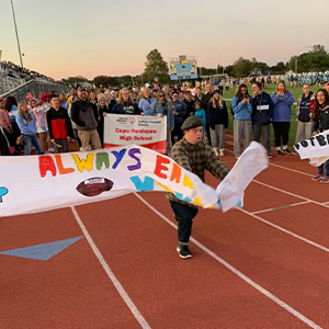 Breaking through the banner at the Cape football game is Davey Frederick.