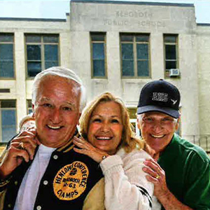 Ron Gray, Gail Stenger, and Scott Walsmith stand in front of their old high school.