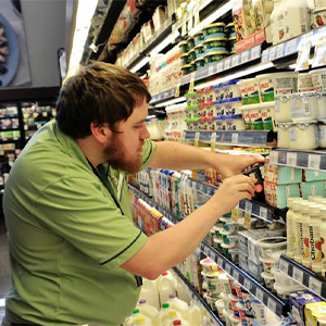 Adam Goss checks for expired products on shelves at Fresh Market in Rehoboth Beach.