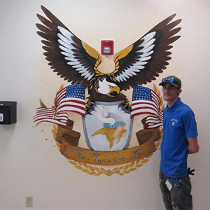 Dan Kimmel shows off the finished mural at Mariner Middle.