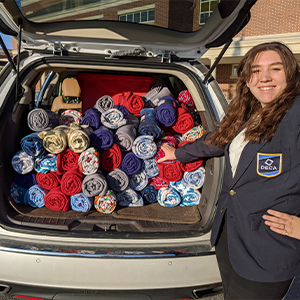 Pointing to a van full of donated blankets is Emily Racz, Cape DECA/BPA president.