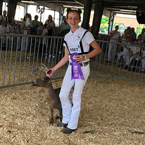 Showing off her grand champion ribbon and award-winning goat is Jetta Hastings.
